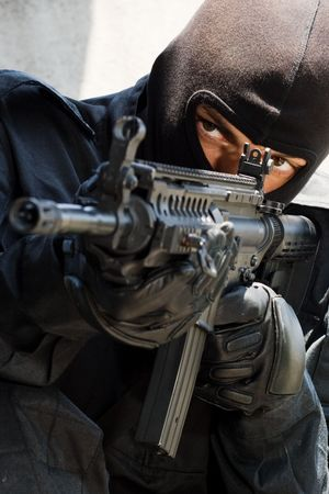 armed forces: Trooper in black mask targeting with an american M-4 gun