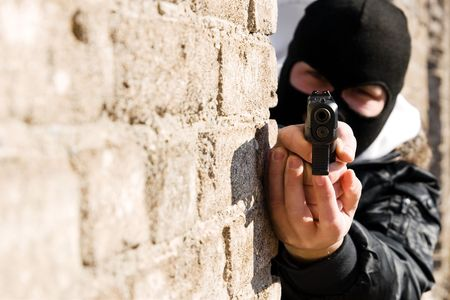 Armed man in black mask pointing a gun in camera photo