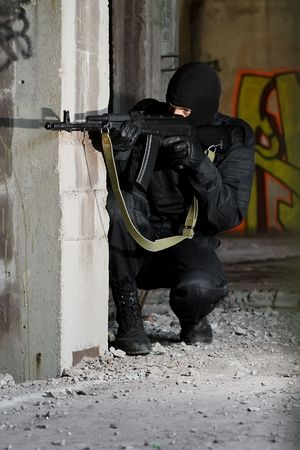 airsoft: Armed criminal shooting with automantic rifle form covered position
