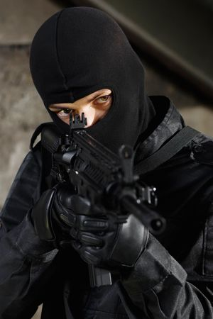 Man in black camouflage targeting with automatic rifle photo