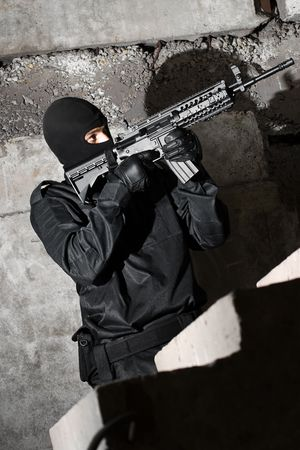 Armed terrorist moving up the staircase with a gun in his hands photo