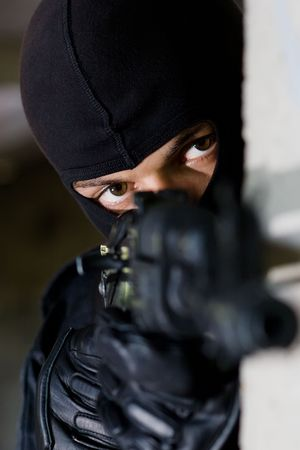 airsoft: Man in black camouflage targeting with an AK-47 automatic rifle Stock Photo
