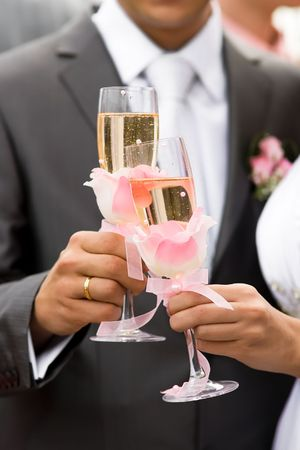 Young family drinking wedding champagne from high glasses