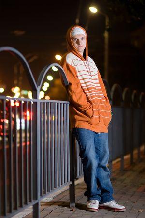 Hip-hop styled teenage guy posing outdoors at night photo