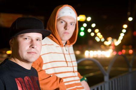 raperos: Hombres j�venes de moda posar al aire libre en las luces de la ciudad