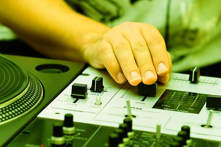 Hand of a disc jockey on the professional mixing controller photo