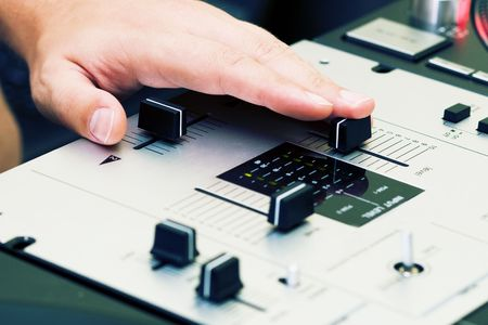 crossfader: Hand of a disc jockey on the professional mixing controller Stock Photo