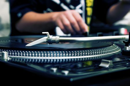 Focus on the professional turntable with a DJ adjusting the volume on controller Stock Photo - 8074988