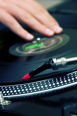 Focus is on the needle and the hand of a disc jockey is on the background photo
