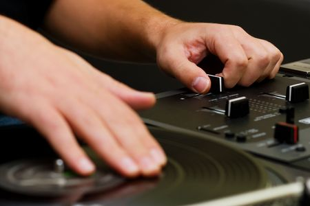 Hands of a disk jockey playing the music on the turntable and top-class mixing controller photo