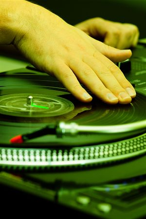 Hands of a disk jockey playin the record on the turntable photo