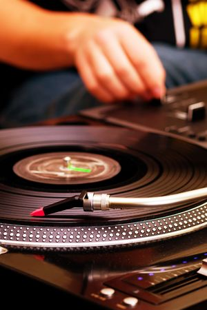 Focus on the professional record player with a DJ adjusting the volume on controller Stock Photo - 8074990