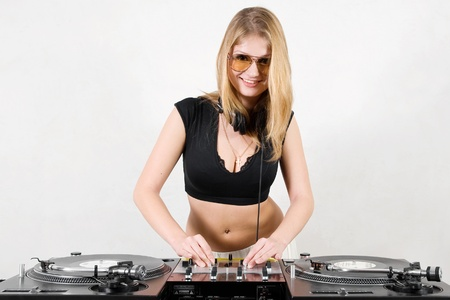 crossfader: Blond girl  mixing the music at the professional equipment