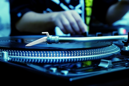 Focus on the professional turntable with a DJ adjusting the volume on controller Stock Photo