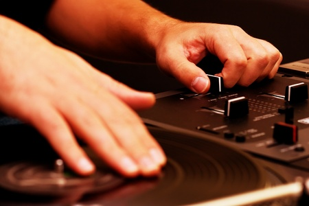 Hands of a disk jockey playing the music on the turntable and top-class mixing controller Stock Photo - 8302686