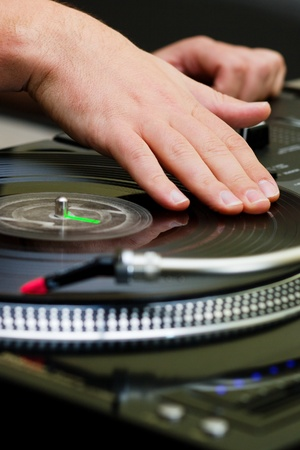 crossfader: Hands of a disk jockey playin the record on the turntable