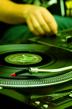 crossfader: Focus on the professional record player with a DJ adjusting the volume on controller