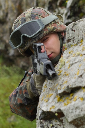 Young warrior hiding behind the rock with a gun photo