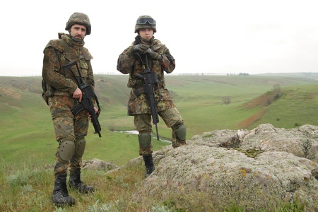 Two soldiers in heavy combative ammuniton on guard Stock Photo - 9534767