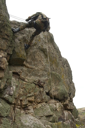 rappeling: Military man does dangerous rappeling in combative ammunition
