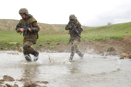 military training: Military men crossing the river under fire Stock Photo