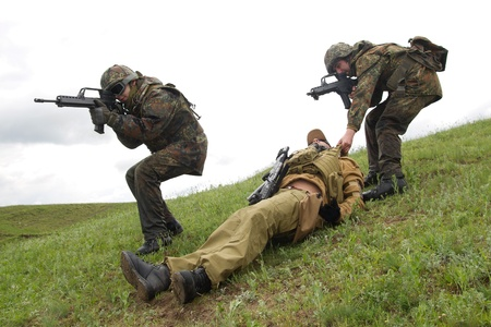 airsoft: Military men protecting injured soldier Stock Photo