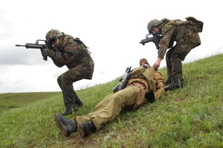airsoft gun: Military men protecting injured soldier Stock Photo