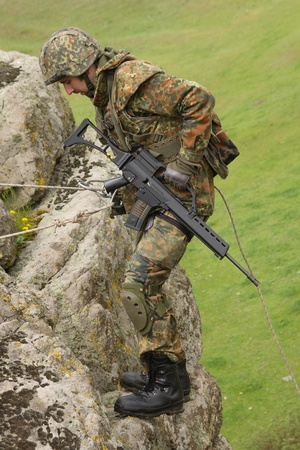 Military man does dangerous rappeling in combative ammunition