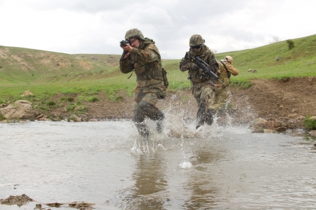 Military men crossing the river under fire Stock Photo