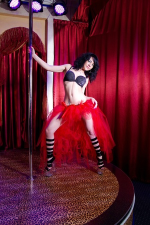 Young attractive woman in lingerie dances strip tease in the adult entertainment club photo