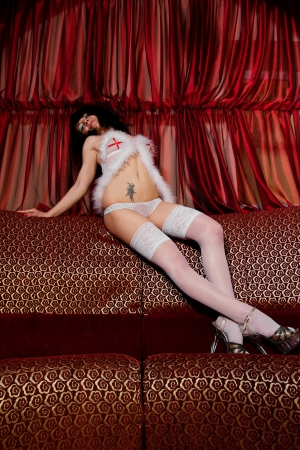 Young attractive woman in lingerie posing on the couch in the adult entertainment club photo