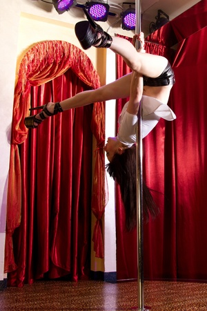 Strip tease dancer hanging on the pole in stripclub photo