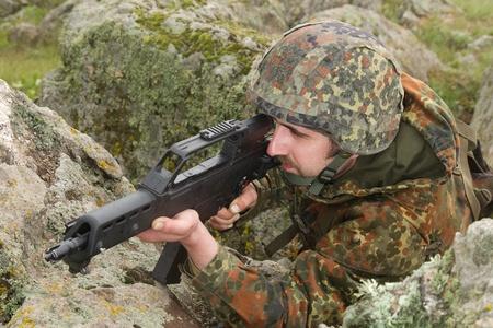 Warrior hiding behind the rock with a gun photo