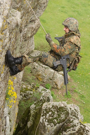 Military man does dangerous rappeling in combative ammunition photo