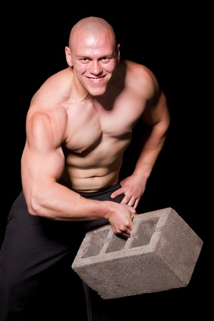 Pumped white guy training with huge brick photo