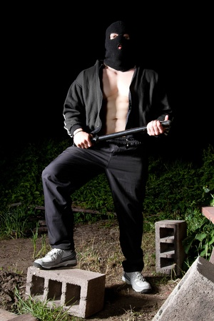 Big athletic thug in black sportive costume and black mask armed with police baton Stock Photo - 9691823