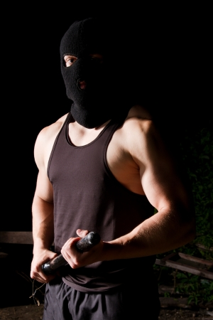 Big athletic thug in black sportive costume and black mask armed with police baton Stock Photo - 9691625
