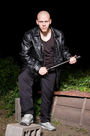 Bald athletic thug in black leather jacket and sportive costume armed with police baton Stock Photo - 9691821