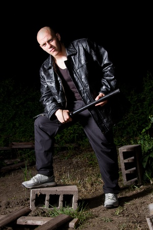Bald athletic thug in black leather jacket and sportive costume armed with police baton photo