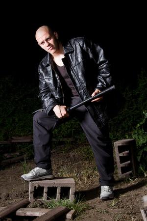 chaqueta de cuero: Thug athletic Calvo en la chaqueta de cuero negro y traje deportivo armados con bast�n de polic�a Foto de archivo