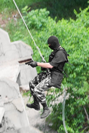 rappelling: Military man in combat equipment does rappelling while assault on the building