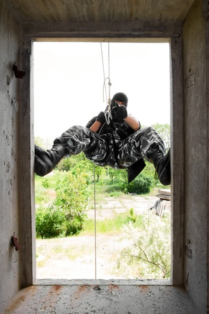 rappelling: Armed man in military uniform hanging on the rope with a gun in his hand while capturing the building
