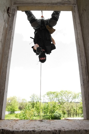 armed forces: Photo of armed man in combat uniform playing terrorist or special forces team member hanging head down on the rope