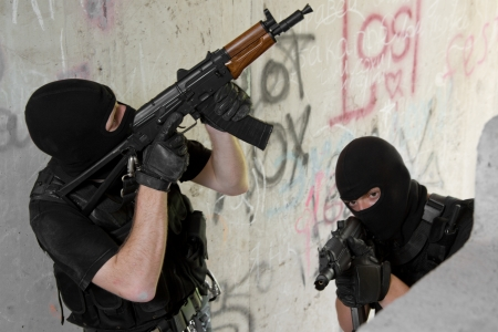 Photo of armed men in combat uniform playing terrorist or special forces team members photo