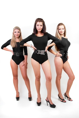 three women: Attractive young females posing in the studio dressed in sexy body-suits with belts and jewelery
