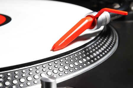 Professional direct-drive turntable record player with white viny timecode and red spheric needle photo