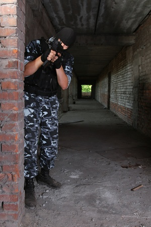 Fully equipped military men with automatic weapons playing strikeball photo