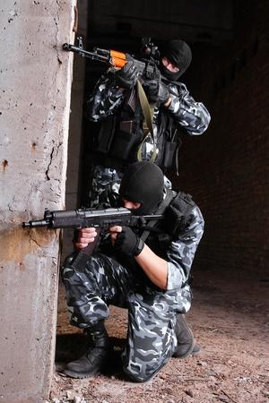 Fotos de soldados equipados pesado o terroristas en máscaras negras con pistolas automáticas.  Foto de archivo - 10886517