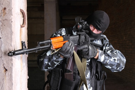 aiming: Photos of heavy equiped soldiers or terrorists in black masks with automatic guns. Stock Photo