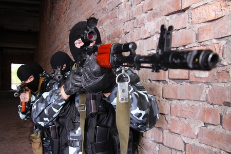 Photos of heavy equiped soldiers or terrorists in black masks with automatic guns. Stock Photo